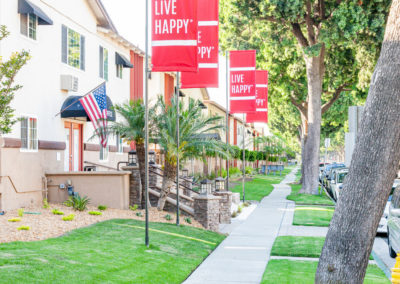Walkway in front of Leasing Office with red Live Happy flags in front of the leasing office
