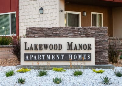 Lakewood Manor monument sign with white rocks and cacti in front