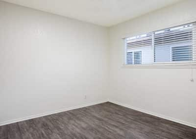 Empty bedroom with wood-like flooring and large window