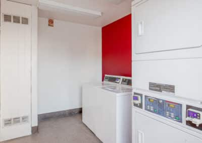 4 Laundry machines in the laundry room with a red wall