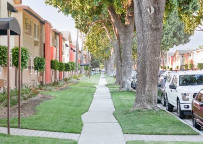 Sidewalk and side view of Lakewood Manor Apartment Homes with lush grass and large trees
