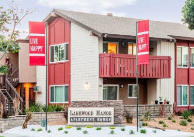Lakewood Manor Monument Sign with two red Live Happy flags