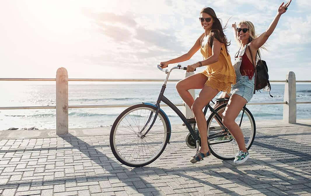 Two female friends on the bike have fun at beach near the lake.